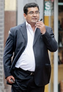 "In this Nov. 26, 2013 photo, Ancash Gov. Cesar Alvarez talks on his cell phone. Alvarez ran a ""mini-dictatorship"" in a state plagued by political murder where the courts and prosecutor's office were ""taken over by criminals,"" Peru's anti-corruption prosecutor alleges. A judge has barred him from leaving the country while more than 100 shelved corruption cases are revived. (AP Photo/Edwin Julca)"